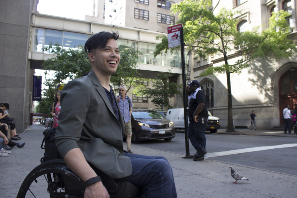 A young man in a wheelchair smiles on a sidewalk in NYC