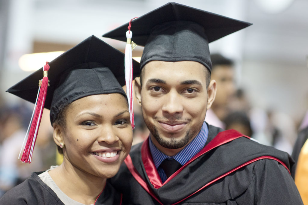 A young man and women smile in CUNY graduation attire