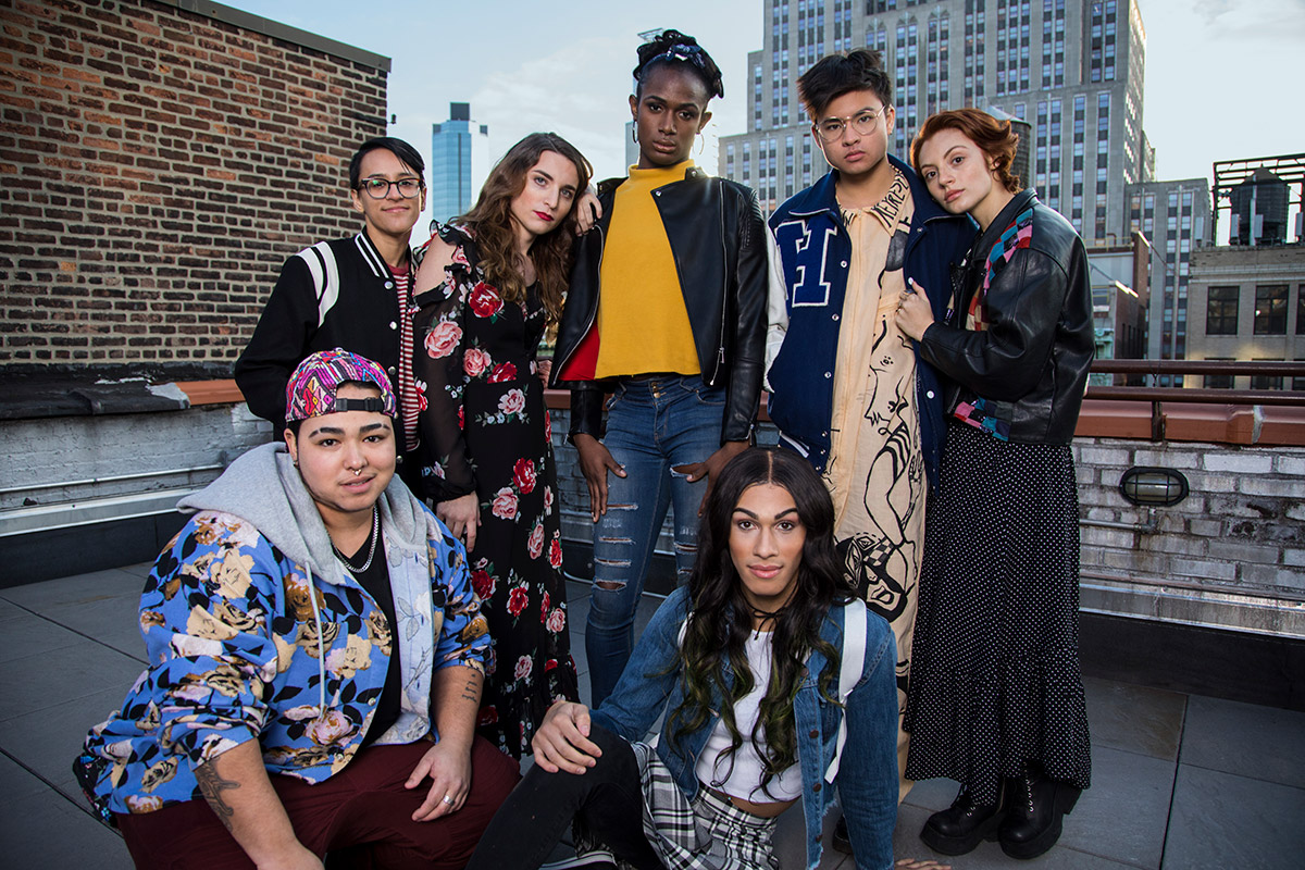 A group of LGBTQ youth posed together on a roof looking strong, proud, and happy