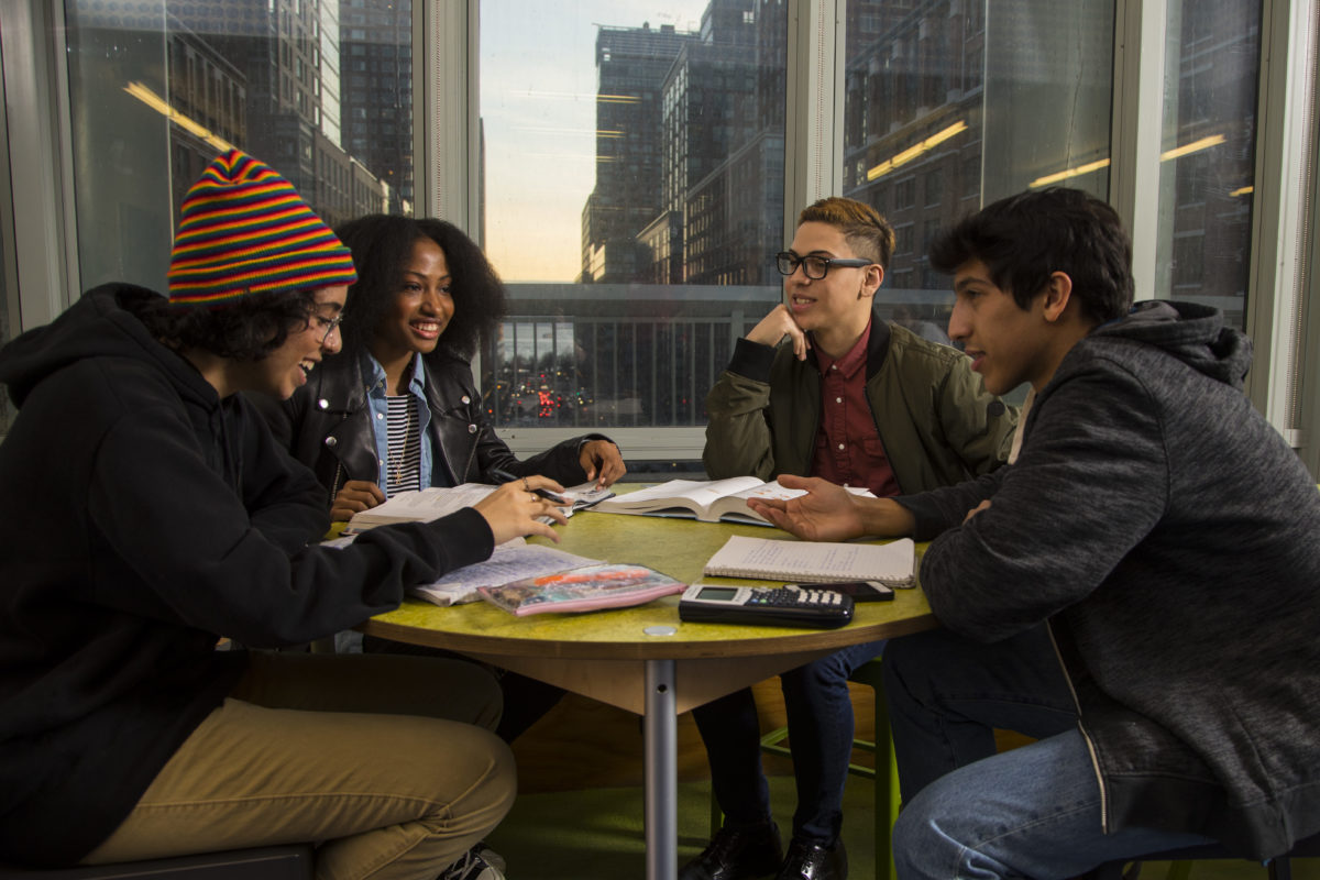 Four students gathered around a table with books and calculators, talking and laughing
