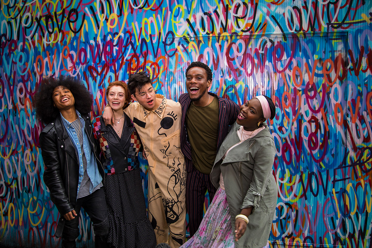 "A group of smiling young people, laughing and smiling in front of a wall that says ""love"""