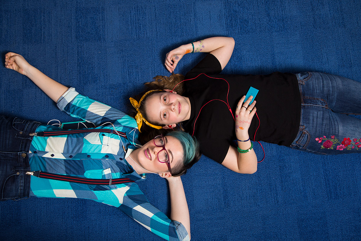 Two young people lying head-to-head on blue carpet, both with headphones in their ears