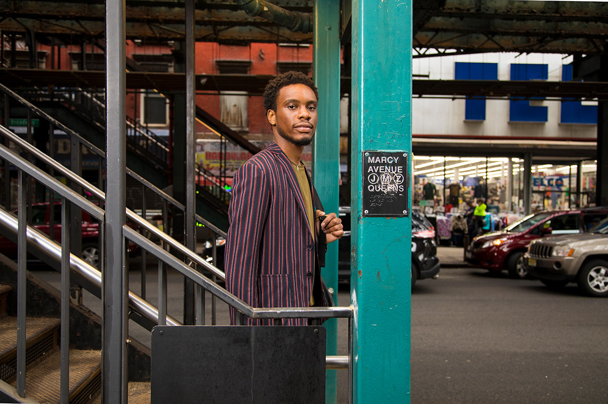 A youth in a striped jacket on the stairs of the Marcy Avenue subway stop in Queens, looking into the camera