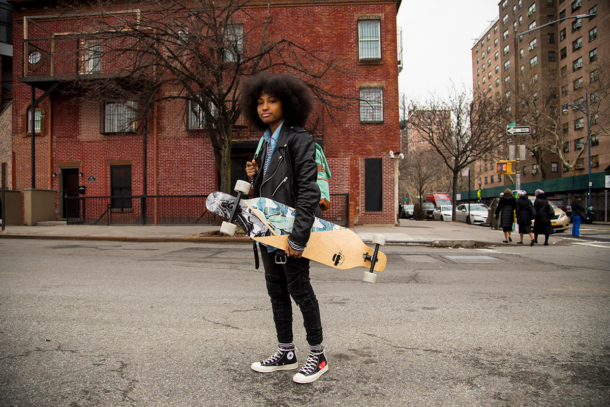 A young person standing on the street in front of a brick building carrying a skate board and a backpack