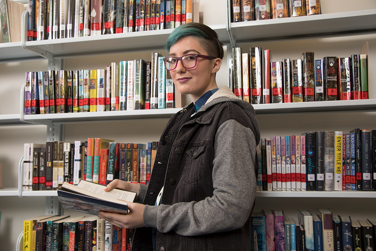 Youth stands in front of book shelves holding an open book and looking at the camera