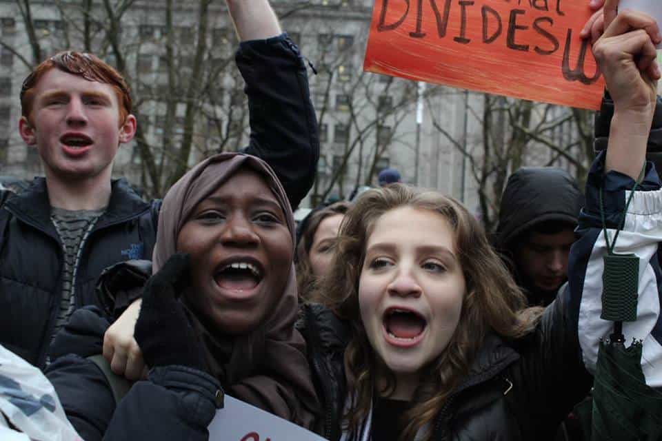 Young women shout and hold up a sign in a crowd of young people.