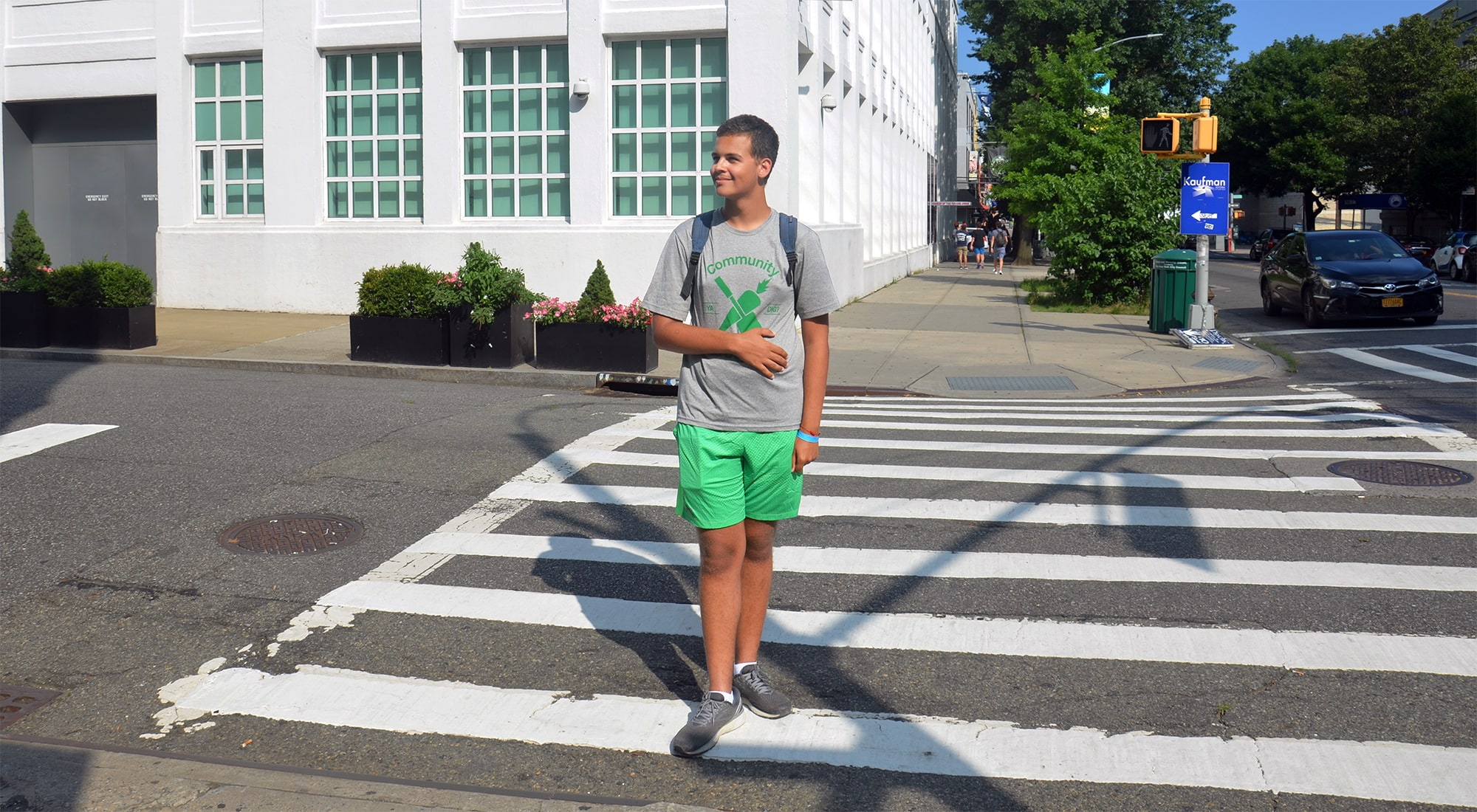 A boy wearing a Community Gardening tee-shirt crosses the street in Astoria, Queens